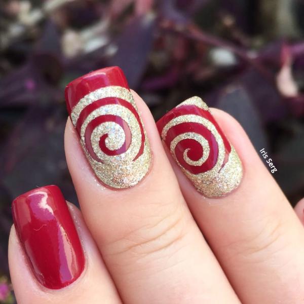 ציפורני ספירלה מהפנטות בשילוב לק אדום נועז וזהב בטקסטורת חול. קרדיט: איריס סרג